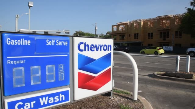 Cheveron gas station in Dallas Texas on July 26 2017 Photographer Cooper Neill Shots CU of Chevron sign and gas price as car passes wider shot of...