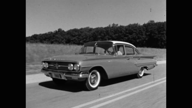 1960 - chevrolet car driving on country road - シボレー点の映像素材/bロール