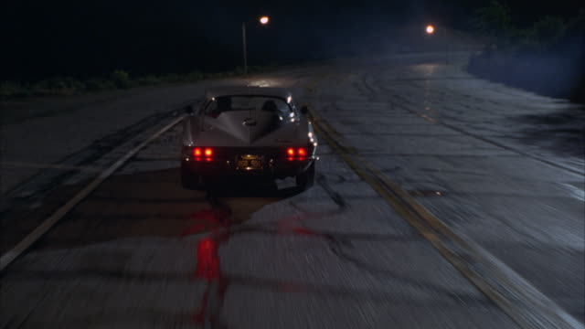 A 1964 Chevrolet Corvette Sting Ray drives on a street and swerves to avoid hitting an oncoming car.