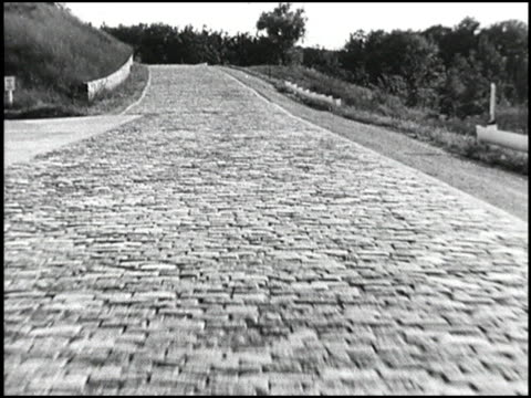 chevrolet deluxe styleline sedan driving on curvy cobblestone road it approaches camera and passes by / ws tracking shot of chevy driving through... - 試運転点の映像素材/bロール