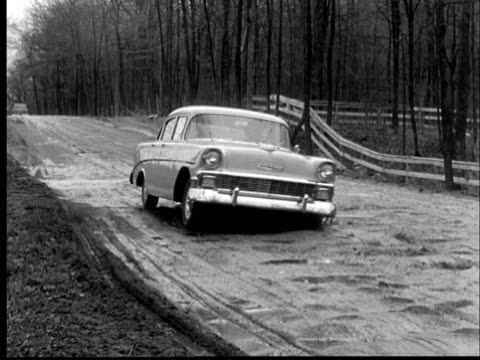 b/w ms pan 1956 chevrolet driving over bumpy muddy road - bumpy stock videos & royalty-free footage