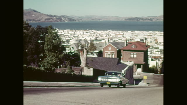 ws pan 1959 chevrolet impala car moving on road up steep hill with city in background / san francisco, california, united states - nordkalifornien stock-videos und b-roll-filmmaterial