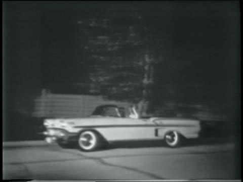 b/w 1958 pan chevrolet impala convertible driving on street at night - 1958 stock-videos und b-roll-filmmaterial