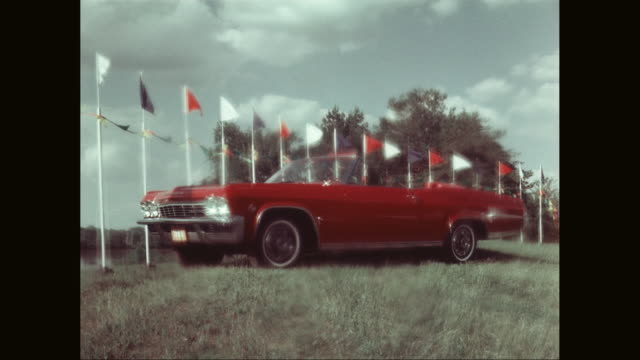 vidéos et rushes de ms chevrolet impala parked in grassy landscape, flags and buntings waving in background / united states  - chevrolet