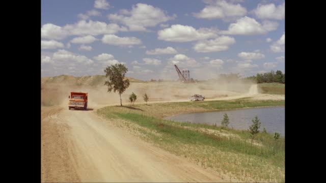 ws 1961 chevrolet pick up truck passes dump truck on dirt track / united states - シボレー点の映像素材/bロール