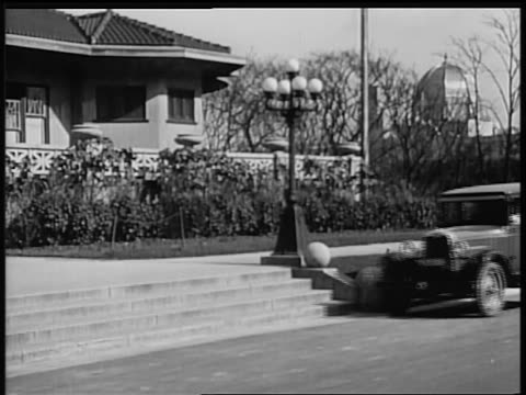 b/w 1928 chevrolet pulling up in front of house / industrial - シボレー点の映像素材/bロール