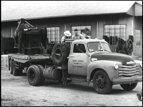 Chevrolet truck hauls heavy industrial equipment on a trailer through mud and on highways Montage 1950 Chevy truck hauling heavy machinery on January...