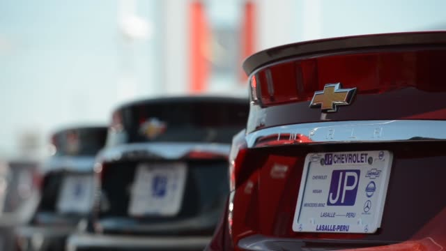 vídeos de stock e filmes b-roll de chevrolet vehicles on the lot at jp chevrolet dealership in peru illinois us close up shots of a chevy medallion on the front and back bumpers of... - para choques