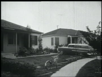b/w 1956 pan chevy nomad station wagon pulling into driveway of suburban home / girls greet father - 1956 stock videos & royalty-free footage