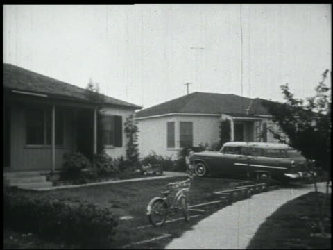 stockvideo's en b-roll-footage met b/w 1956 pan chevy nomad station wagon pulling into driveway of suburban home / girls greet father - 1956