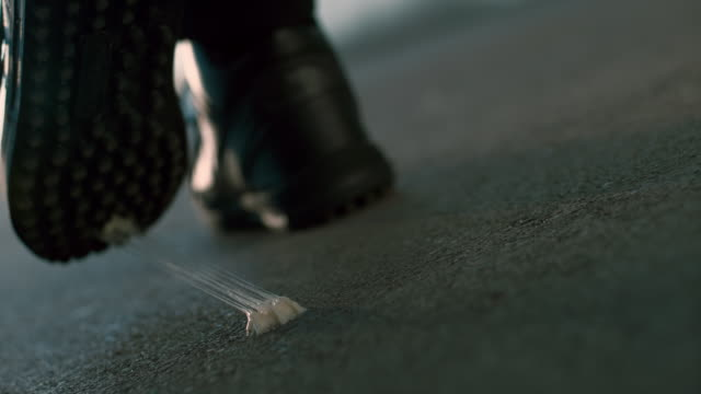 slo mo ld chewing gum sticking onto the sole of a shoe in the street - bubble gum stock videos & royalty-free footage