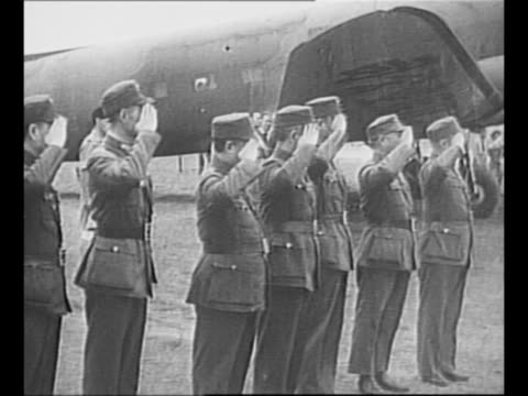 chiang kaishek and madame chiang deplane greet official on tarmac / soldiers salute as plane stands in background / pan b29 flying tiger planes on... - chiang kai shek stock-videos und b-roll-filmmaterial