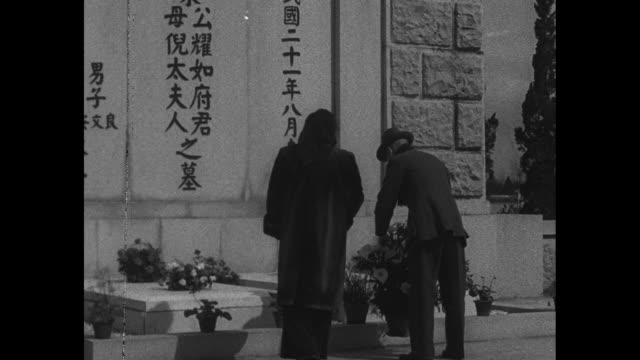 chiang kaishek and wife arrive at cemetery to leave basket of flowers / general and mrs chiang pay their respects and bow repeatedly then leave to... - chiang kai shek stock videos and b-roll footage
