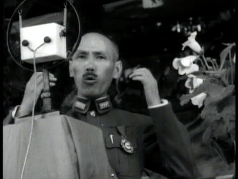 chiang kai-shek on podium standing behind microphone speaking gesturing. huge crowd of soldiers & people standing. - chiang kai shek stock videos & royalty-free footage