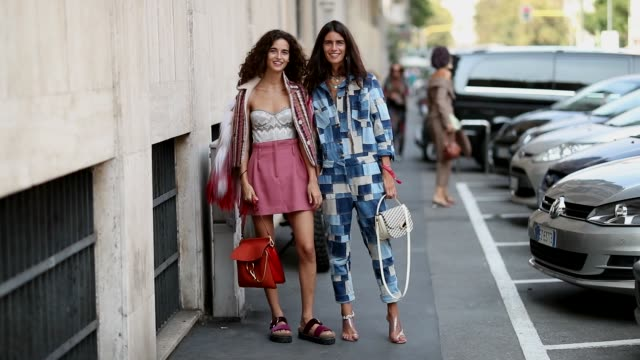 vídeos de stock e filmes b-roll de chiara scelsi wearing pink mini skirt sandals fake fur jacket and chiara totire wearing denim overall with pattern during milan fashion week... - sandália