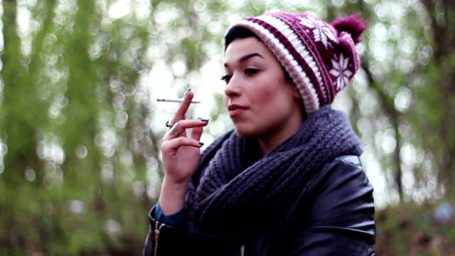a chic adolescent girl with a funny cap enjoying smoking a cigarette - cigarette stock videos & royalty-free footage