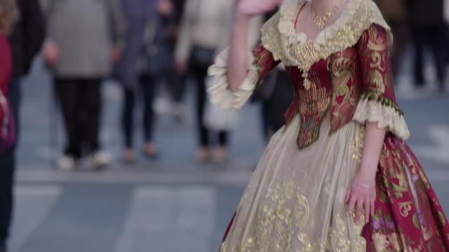 Chica joven vestida de fallera sonríe y saluda a la cámara