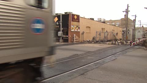 """chicago brown line train, part of the chicago """"l"""" system, speeds by on street level-tracks after boom gate lowers. - chicago 'l' stock videos & royalty-free footage"""