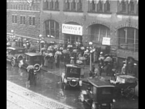 stockvideo's en b-roll-footage met ext chicago coliseum as people wait to enter building for 1916 republican national convention many hold umbrellas mounted policeman stands on rainy... - intellectueel eigendom