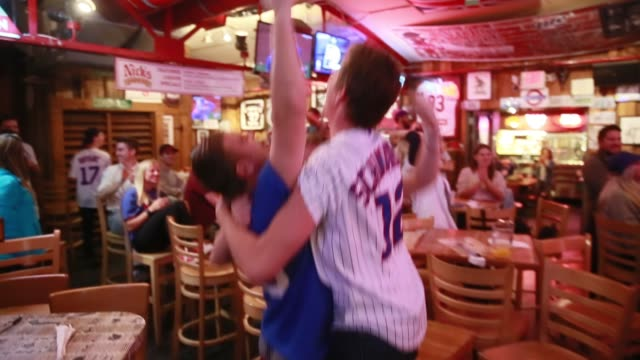Chicago Cubs fans at Nick's English Hut in Bloomington Indiana watch and react as their team plays the Cleveland Indians eventually winning the first...