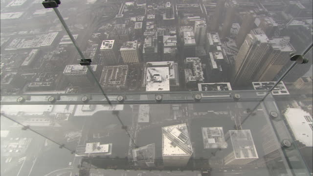 chicago downtown rooftops appear through the glass floor and walls of a viewing platform on the sears tower. - sears tower stock-videos und b-roll-filmmaterial
