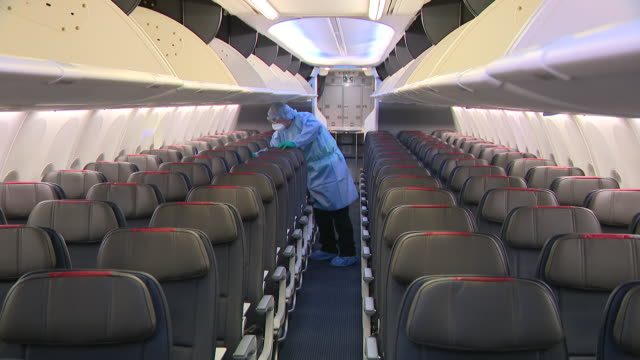 chicago, il, u.s. - american airlines employee in ppe disinfects airplane interior amid coronavirus pandemic on tuesday, june 30, 2020. the same day... - cleaning stock videos & royalty-free footage
