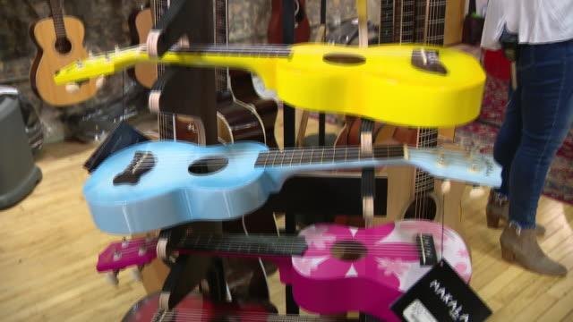 vídeos de stock, filmes e b-roll de chicago, il, u.s. - assorted guitars at guitar works, a guitar shop in evanston, il amid coronavirus pandemic on saturday, september 12, 2020. guitar... - ukulele