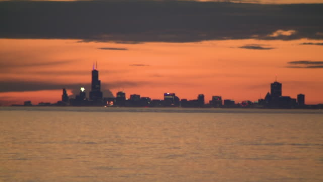 wgn chicago il us chicago skyline seen across lake at sunset view from marquette park beach in gary indiana on monday may 25 - romantic sky stock videos & royalty-free footage