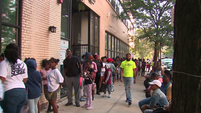 chicago, il, u.s. - children waiting in line to receive free haircut and backpacks at back-to-school event, on monday, sep 2, 2019. - back to school stock videos & royalty-free footage