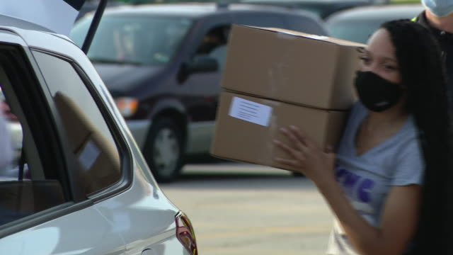 vídeos y material grabado en eventos de stock de chicago, il, u.s. - close-up of food boxes provided by northern illinois food bank, woman loading boxes into car. as the pandemic continues into its... - ansiedad