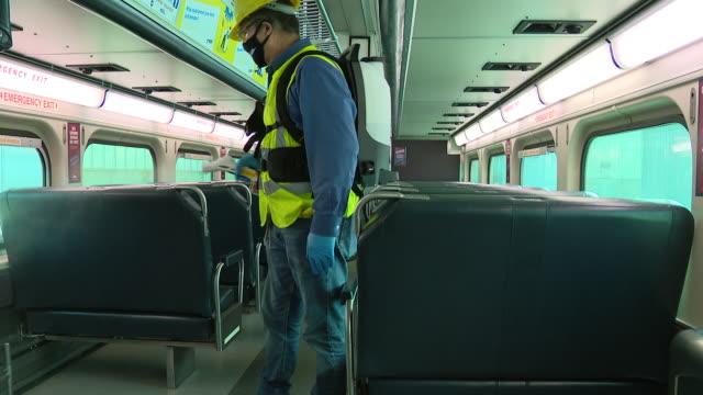 vídeos de stock e filmes b-roll de chicago, il, u.s. - employee disinfects metra train inferior at metra's western avenue coach yard in chicago on tuesday, september 15, 2020. - enfeites para a cabeça