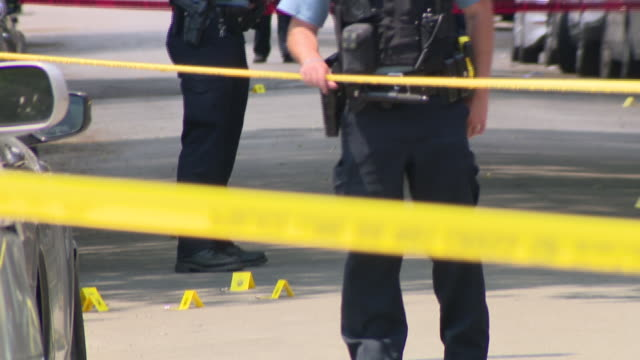 stockvideo's en b-roll-footage met chicago, il, u.s. - evidence markers at crime scene. on chicago's west side where three people were shot. on wednesday, june 17, 2020. - afzetlint