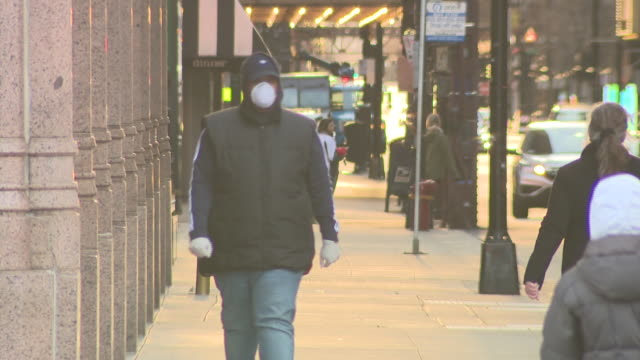 chicago, il, u.s. - few pedestrians walking in downtown and wearing protective masks during covid-19 pandemic, on thursday, march 25, 2020. - pedestrian stock videos & royalty-free footage
