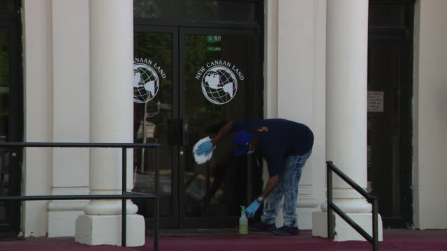 chicago, il, u.s. - man disinfecting new canaan land missionary baptist church glass door on chicago's south side on sunday, may 24, 2020. - baptist stock videos & royalty-free footage