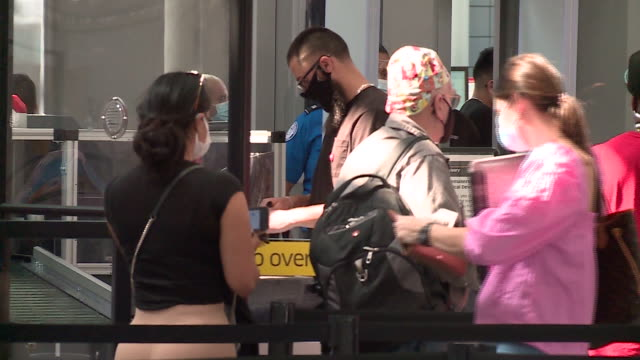 chicago, il, u.s. - masked people going through security check at chicago's o'hare airport during the covid-19 pandemic, at the beginning of labor... - セキュリティスキャナ点の映像素材/bロール