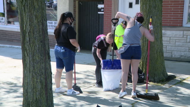 chicago, il, u.s. - members of community cleaning street. a curfew is now in effect in cicero where a state of emergency was declared, after a deadly... - müllsack stock-videos und b-roll-filmmaterial