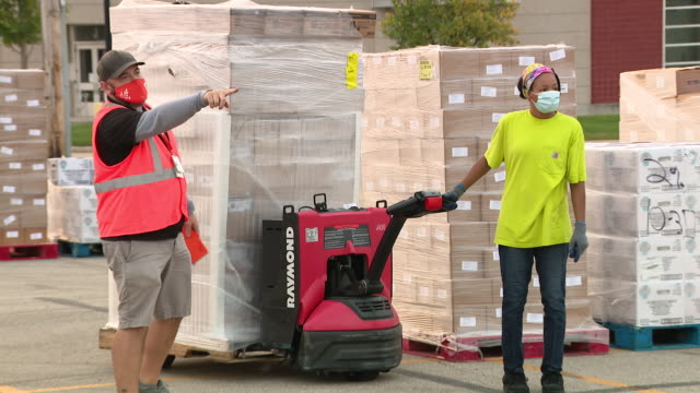 chicago, il, u.s. - pallets of food boxes being stacked for northern illinois food bank pop-up market event. as the pandemic continues into its... - scaricare video stock e b–roll