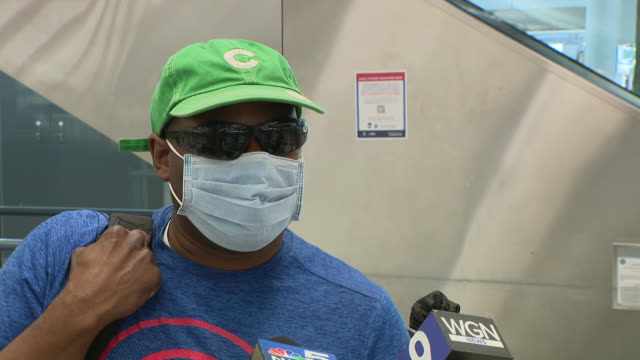 wgn chicago il us passenger in mask speaks about selfquarantine order at o'hare airport on monday july 6 2020 anyone arriving in chicago after... - 野球帽点の映像素材/bロール