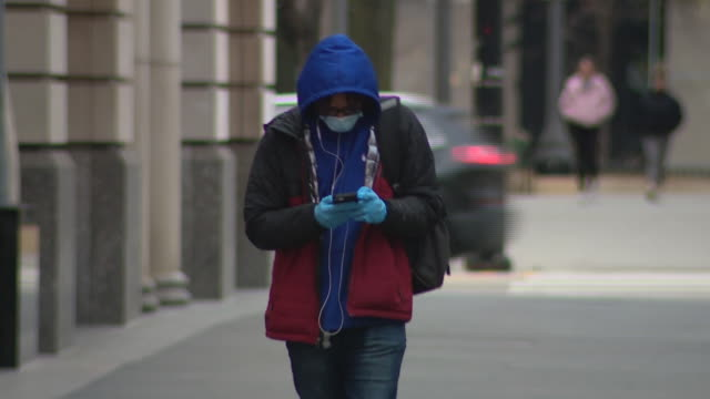 chicago, il, u.s. - pedestrians walking in distance to each other wearing protective masks during covid-19 pandemic, on thursday, march 25, 2020. - pedestrian stock videos & royalty-free footage