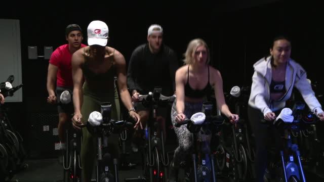 chicago, il, u.s. - people exercising at stationary bike workout class at cyclebar river north on sunday, january 5, 2020. - インドアサイクリング点の映像素材/bロール