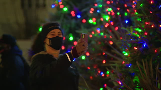 chicago, il, u.s. - people in masks taking selfies near christmas tree illuminated after virtual lighting ceremony in millennium park, on thursday,... - christmas tree lighting ceremony stock videos & royalty-free footage