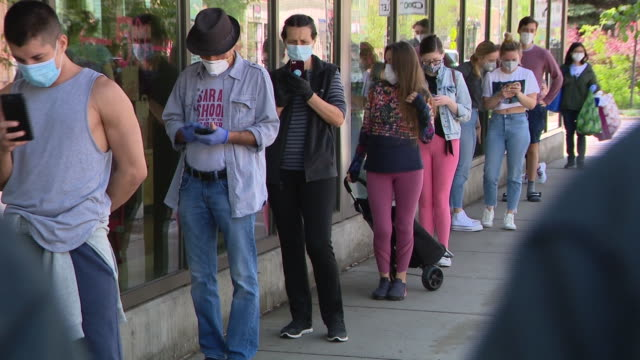 vidéos et rushes de chicago, il, u.s. - people listening to music while queuing outside of trader joe's in chicago's lakeview neighborhood on friday, may 15, 2020. - file d'attente