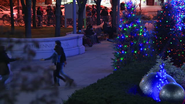 chicago, il, u.s. -people walking near christmas tree illuminated after virtual lighting ceremony in millennium park, on thursday, november 19, 2020.... - christmas tree lighting ceremony stock videos & royalty-free footage