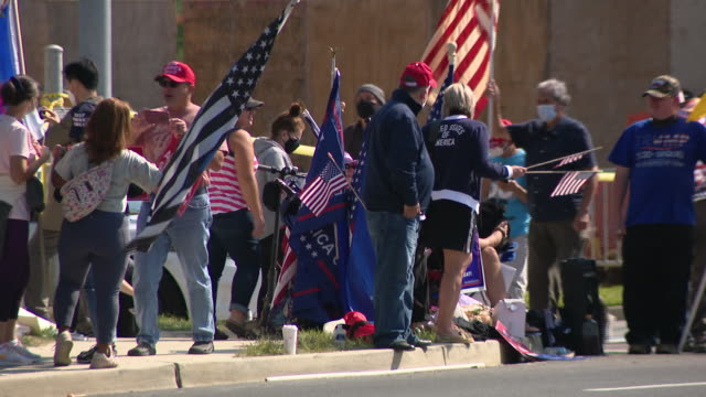 chicago, il, u.s. - people with flags and maga merchandise waiting for donald trump's car to arrive on sunday, october 4, 2020. - ベセスダ点の映像素材/bロール