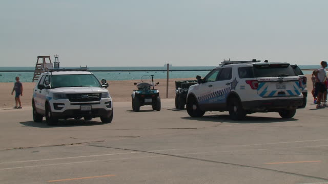 wgn chicago il us police officers guarding beach after crowds cluttered closed lakefront beaches chicago police had been out patrolling warning... - seeufer stock-videos und b-roll-filmmaterial