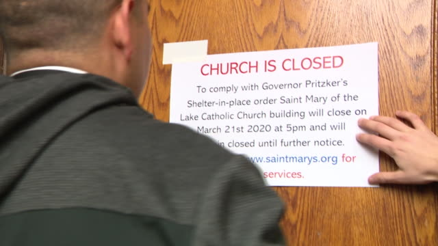 chicago, il, u.s. - priest sticking information sign at saint mary of the lake catholic church doors. the archdiocese of chicago is suspending all... - information sign stock videos & royalty-free footage