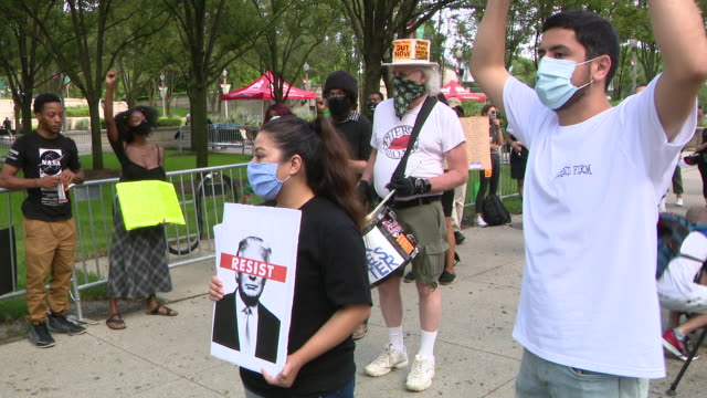 vidéos et rushes de wgn chicago il us protestors with placards man playing drum rally in chicago's millennium park followed by a march to trump tower to protest trump's... - écriture européenne