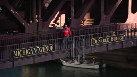 chicago, il, u.s. - raised michigan avenue dusable bridge across the chicago river and employee in reflecting clothing on sunday, august 16, 2020. - 跳開橋点の映像素材/bロール