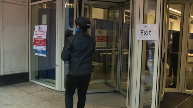 chicago, il, u.s. - signage in front of polling place, man entering and exiting after giving his vote. early voting in chicago on day before 2020... - western script stock videos & royalty-free footage