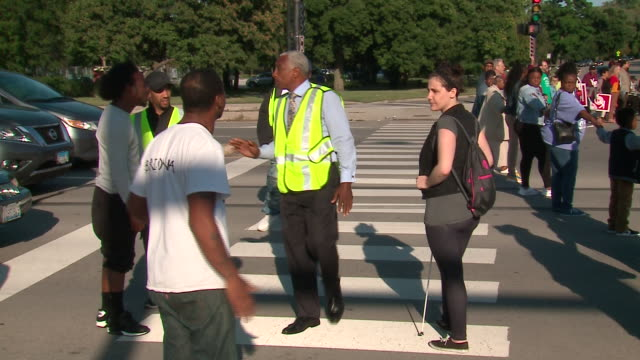 wgn chicago il us supporters of the community benefits agreement blocking traffic on street during rally to demand chicago's mayor lori lightfoot... - holding hands stock videos & royalty-free footage
